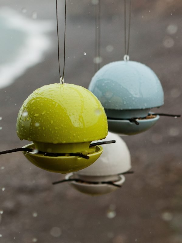 3 ceramic Birdball seed feeders in white, blue and lime green hanging in the rain