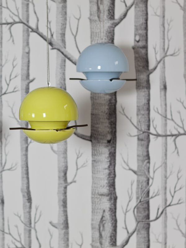 Blue and lime green Birdball seed feeders hanging in front of stylised wallpaper of sketched tree trunks