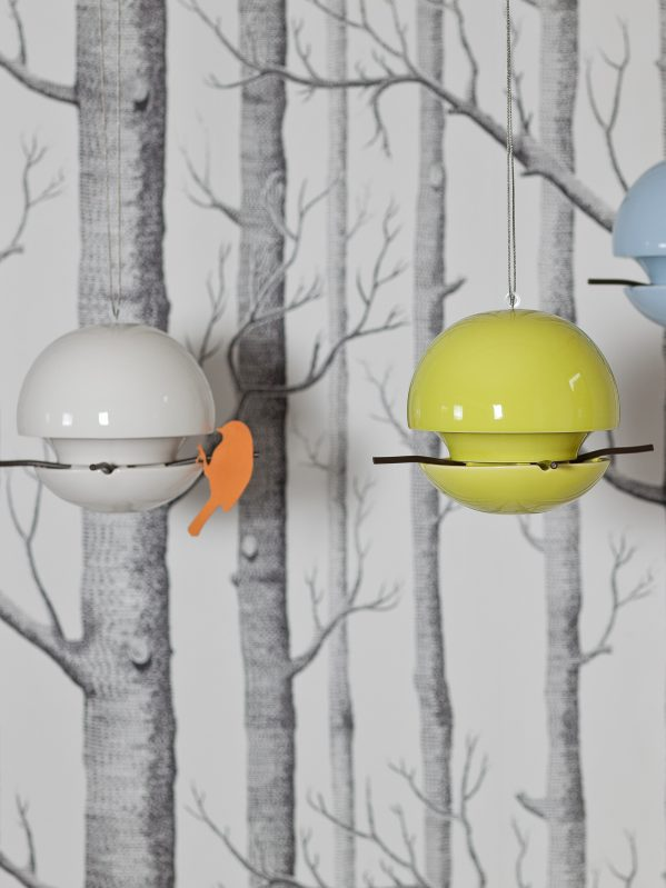 2 ceramic Birdball seed feeders hanging in front of wallpaper with sketched tree trunks.